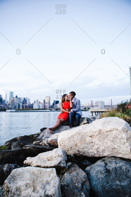 Wide shot of a joyous young couple about to kiss seated over the boulders by waterfront
