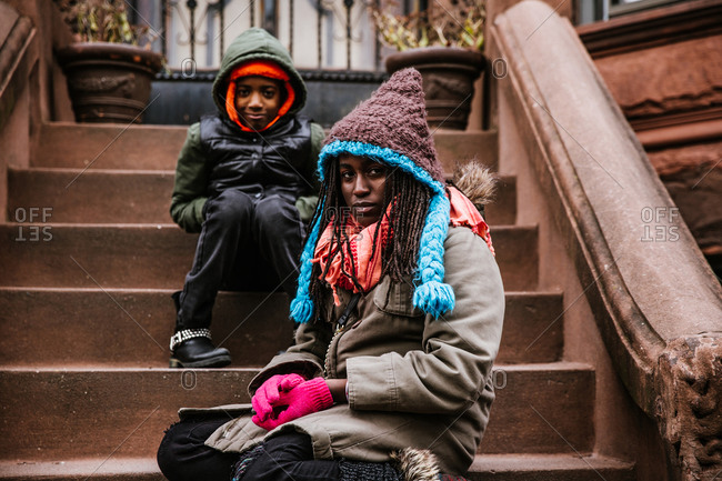 Horizontal shot of young siblings sitting on porch in winter clothing looking at the camera