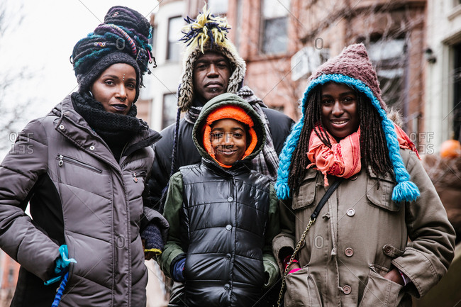Horizontal waist up shot of a family of four outside huddled in the cold look at the camera