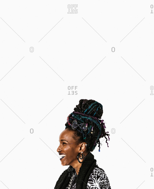 A side profile portrait shot of a laughing black woman with colorful dreadlocks