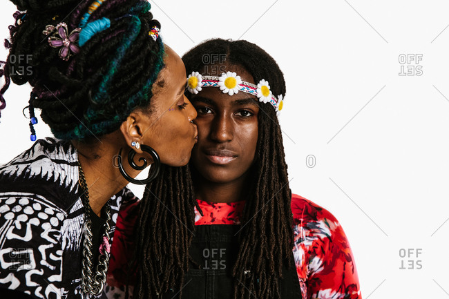 A medium shot of an african american mom kissing her daughter on the cheek
