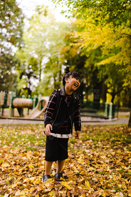 A portrait shot of a young Asian girl with pigtails laughing while standing on the leaves in a park