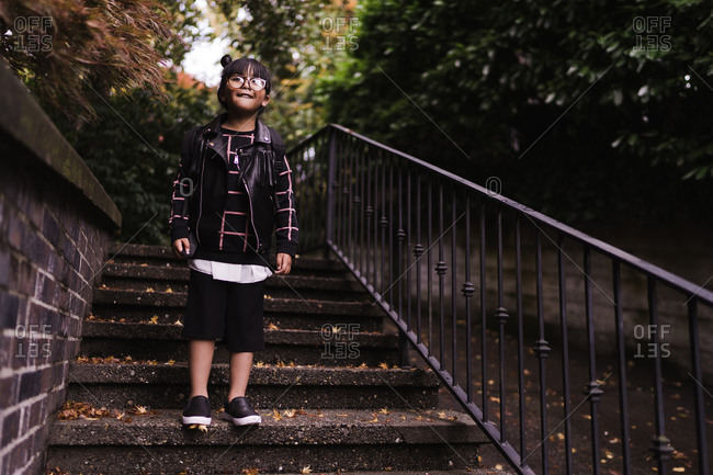 A medium shot of a happy young Asian girl with pigtails wearing glasses and a school bag standing on stairs of a park
