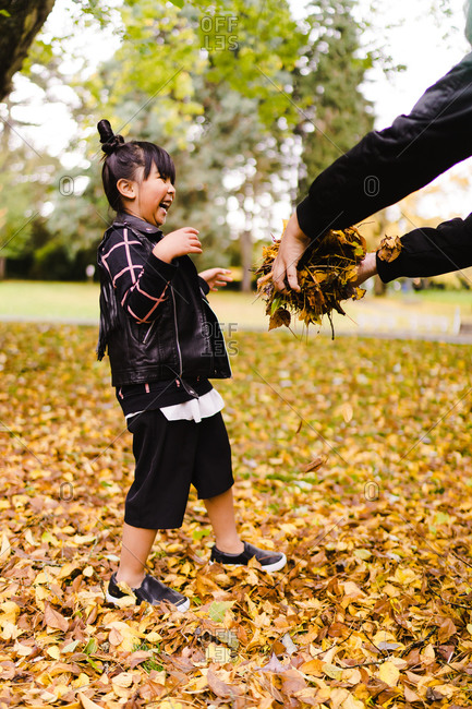 A portrait shot of a happy young Asian girl with pigtails playing with leaves in a park