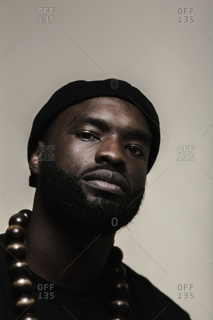 A close up shot of an African American man with beard wearing a black beanie cap posing with a big beads necklace