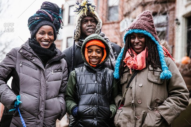 A close up shot of a smiling black family in winter coats on holiday