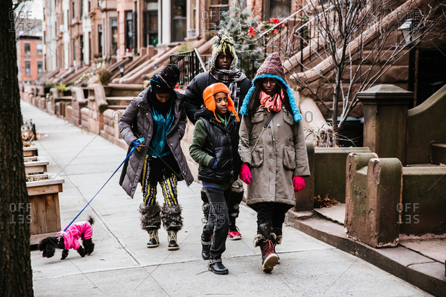 Colorful black family of four walking dog in winter coats on city sidewalk