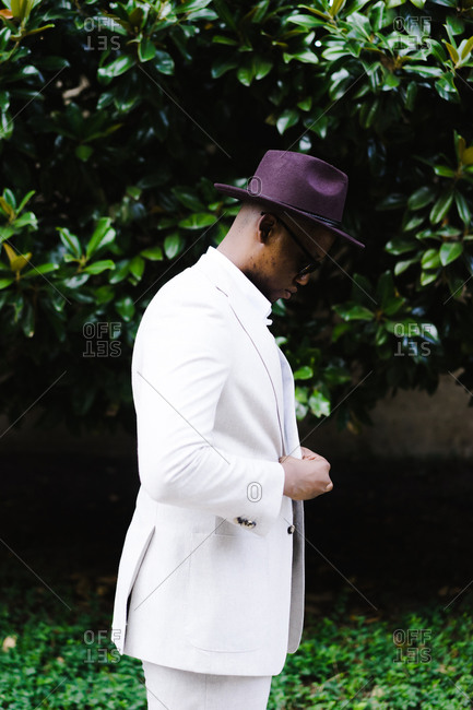 A side profile portrait shot of african american man in a white suit and purple hat