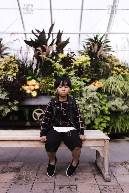 Young Asian girl pouting while sitting on bench in a greenhouse