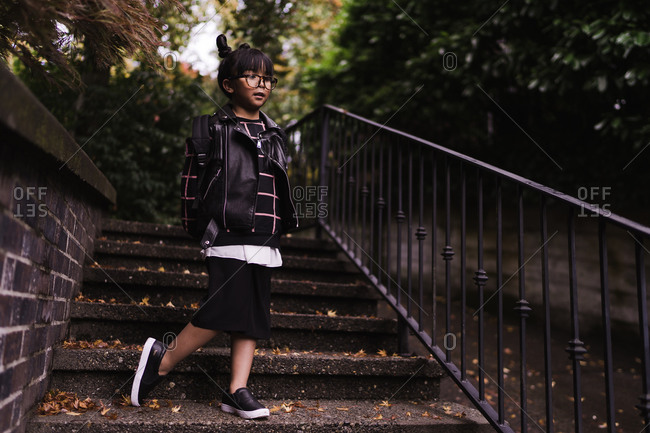 A portrait shot of a young Asian girl with pigtails wearing glasses and a school bag standing on stairs of a park