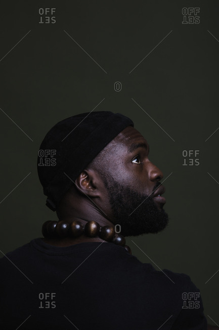 A side profile back shot of a serious African American man wearing a black beanie cap posing with a big beads necklace against a green background