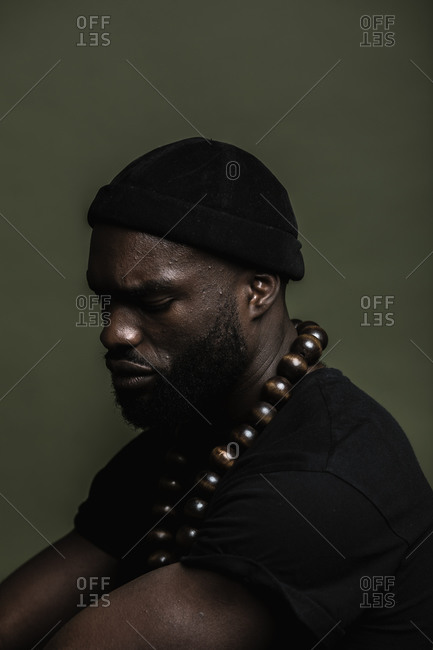 A side profile shot of a serious African American man wearing a black beanie cap posing with a big beads necklace against a green background