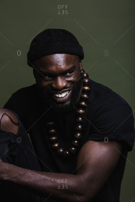 A portrait shot of a smiling African American man wearing a black beanie cap posing with a big beads necklace against a green background