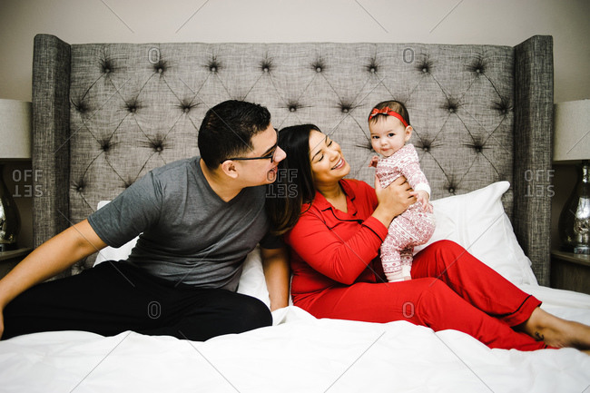 Horizontal shot of joyous latino parents playing with their daughter with the mother holding the girl on the bed