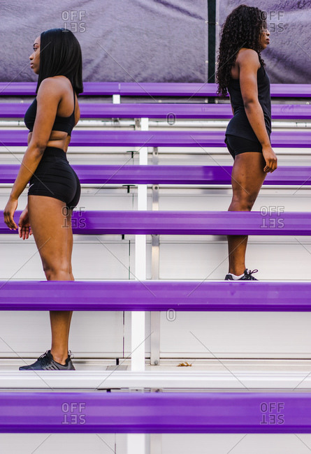 Vertical profile shot of two black women standing facing opposite sides on a track field