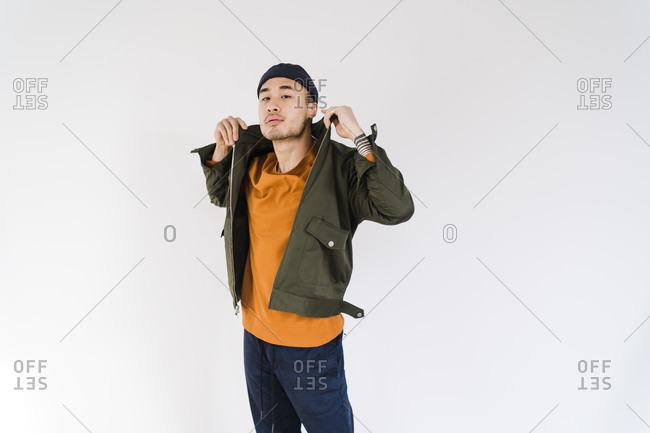 Horizontal shot of a stylish Asian man wearing a green jacket and orange t-shirt and posing
