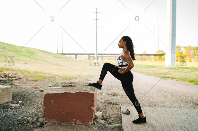 Black woman warming up outdoors and stretching hip flexors on a concrete block