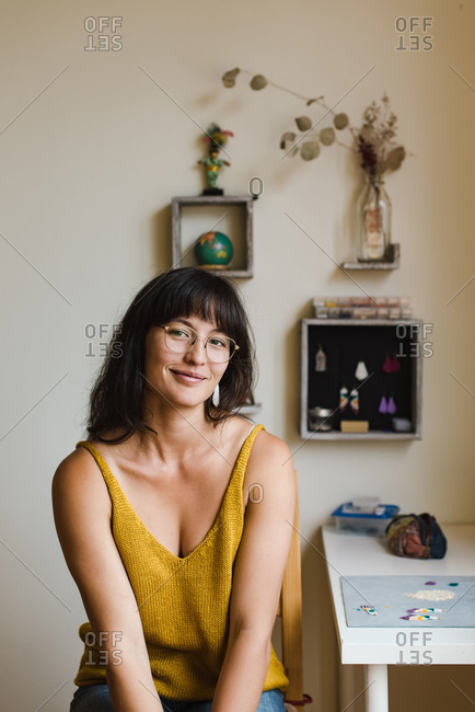 Young, confident mixed race jewelry designer sitting on her chair next to the desk and posing between work