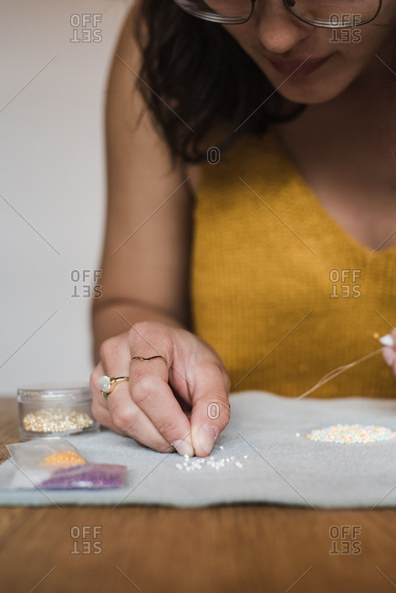 Vertical close up on the hand of a mixed race woman making her own jewelry at home