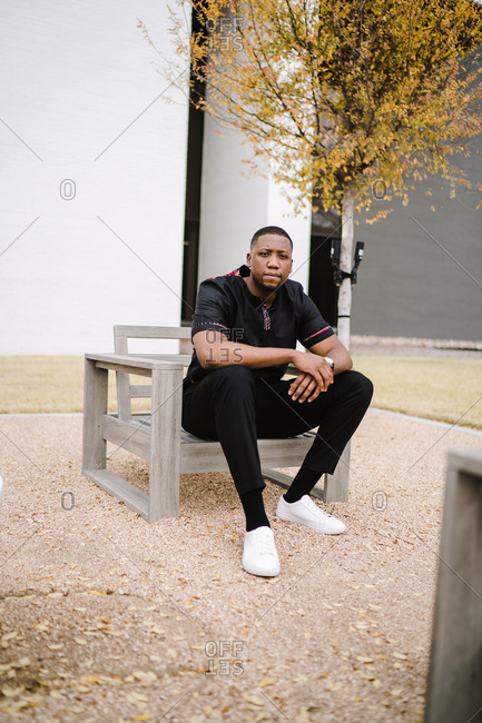 Confident black man in black leisure wear sitting on a chair in the park with arms crossed over each other