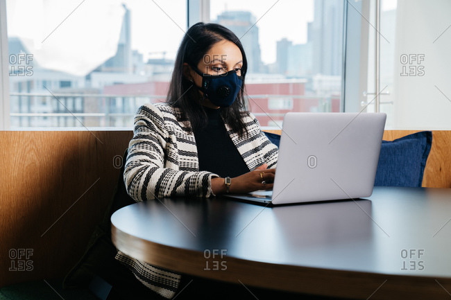 Indian female lawyer typing on a laptop in her office with a face mask on