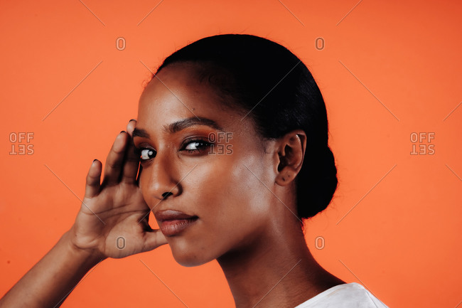 Headshot of an attractive black, Ethiopian woman with tied hair and looking at the camera against an orange backdrop