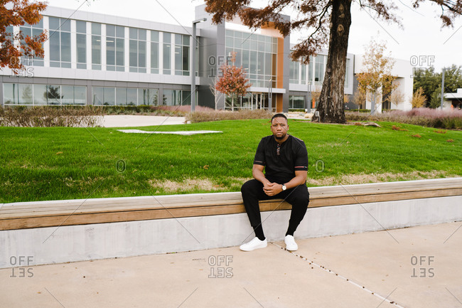 Black man with a muscular physique sitting in a park with arms crossed over each other