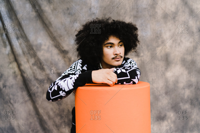Horizontal shot of a stylish Asian man with curly hair leaning over an orange stool and looking sideways