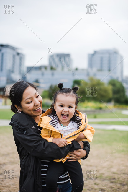 Portrait of a mother holding her playful little girl