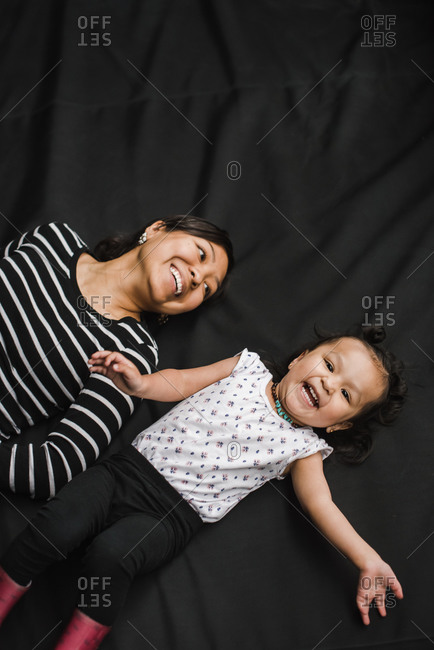 Happy mother and daughter laughing while laying on a black background