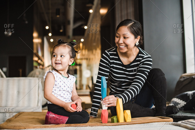 Smiling mother and daughter playing with wooden blocks while sitting on a mat