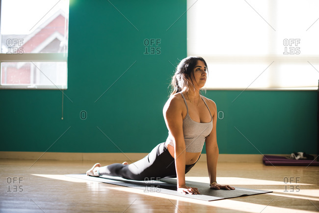 Strong Young Mixed race woman doing cobra pose on a yoga mat