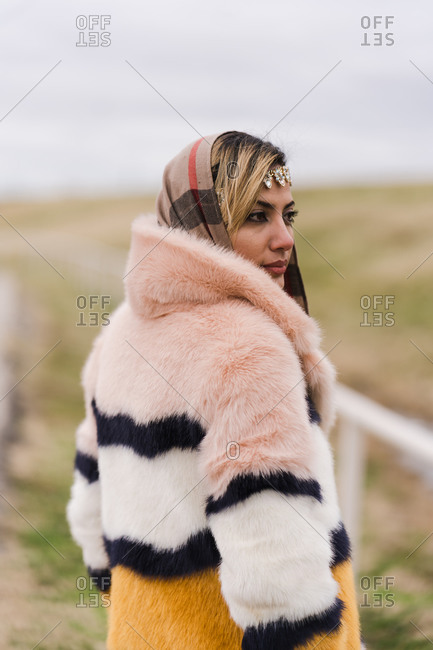 Stylish Muslim woman standing  outdoors and posing in her beautiful fur coat