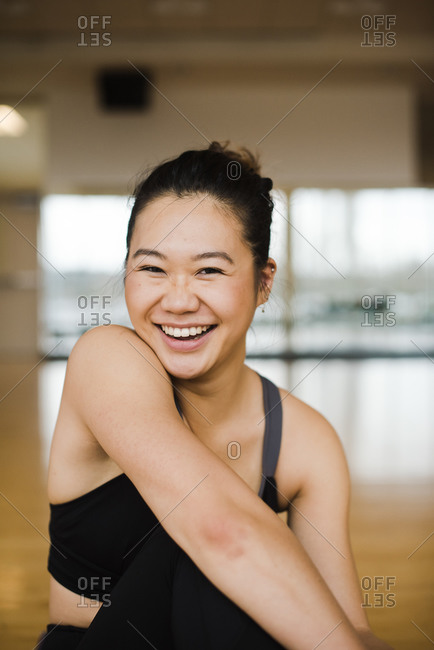 Portrait of a smiling woman doing yoga in a studio