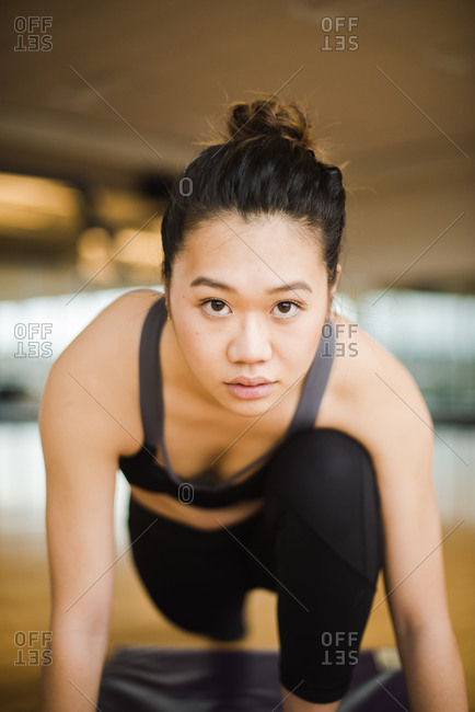 Vertical portrait of a young confident woman doing yoga on a mat in the gym
