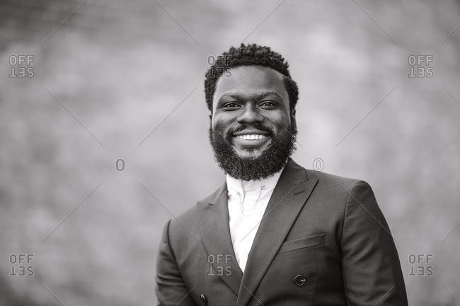 A black and white close up shot of a smiling black man in a suit