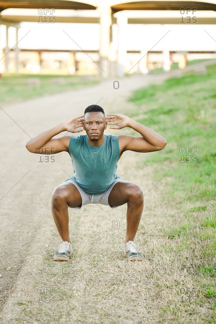 Athletic man doing exercise outdoors on an empty track