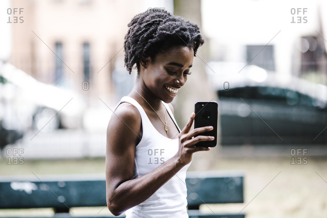 Woman smiles as she clicks a photo on her phone while standing outdoors