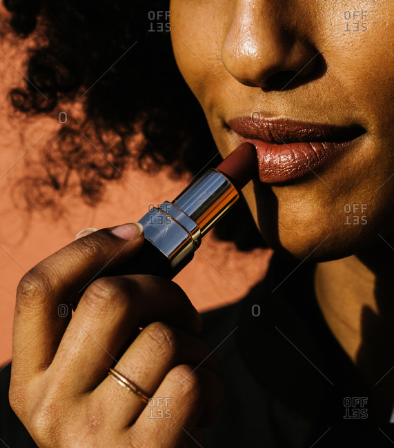 Vertical close up shot of a woman with curly hair putting on lipstick