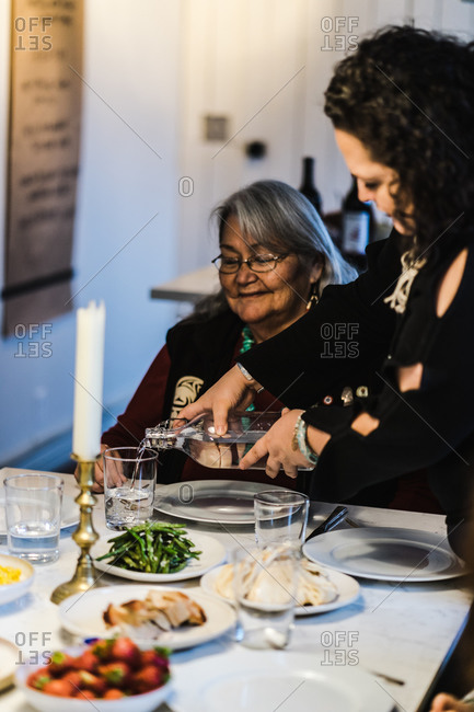Vertical shot of a woman serving water to her grandmother at family dinner at home