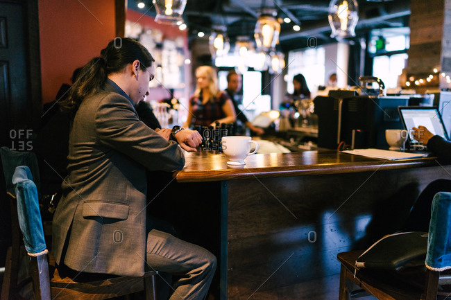 Horizontal shot of a businessman checking time on his watch in a cafe