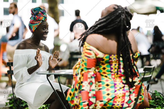 A medium shot of happy two black women sitting at a table outside