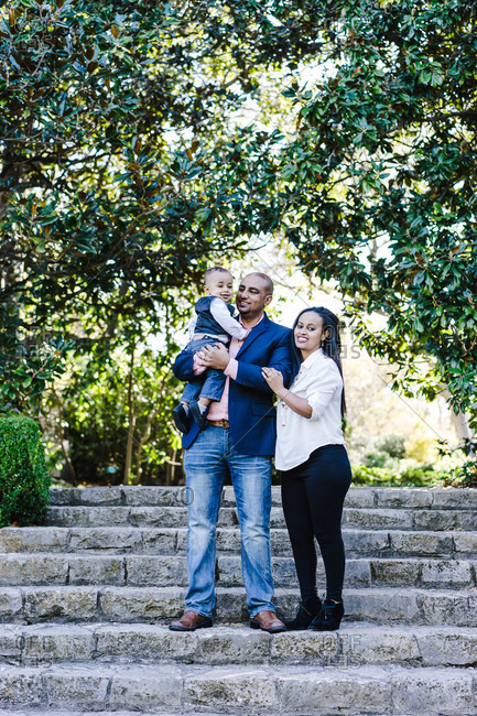Vertical portrait of a family with their little son in a park