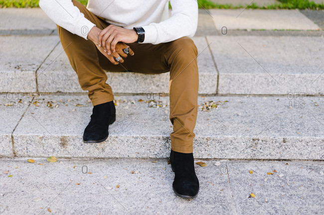 Horizontal shot of lower section of a black man sitting over steps outside