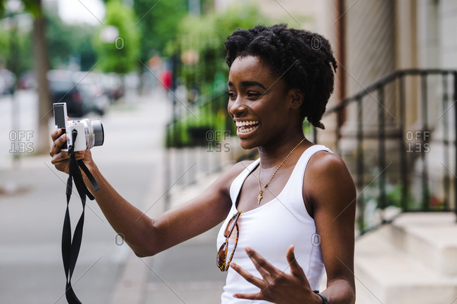 Black woman smiling and shooting herself on a digital camera