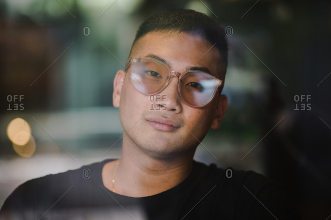 Portrait of an Asian man in his office with the window reflection in the foreground