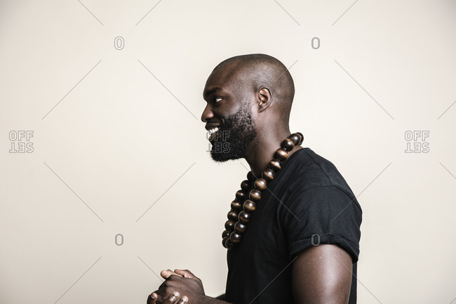 Profile view of an African American man posing in front of light background