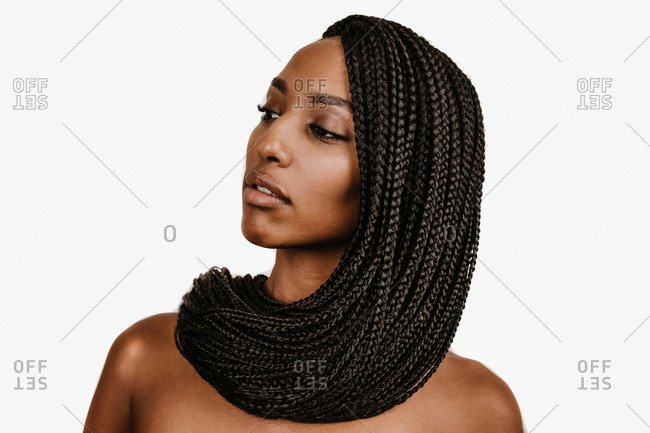 A close up shot of a young black woman with long braid extensions looking sideways