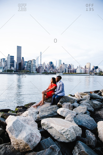 Wide shot of a young couple in smart casuals sitting over the rocks by waterfront look sideways