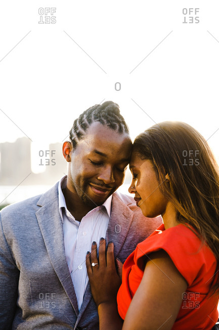 Vertical waist up shot of a young couple with eyes closed embracing near a waterfront